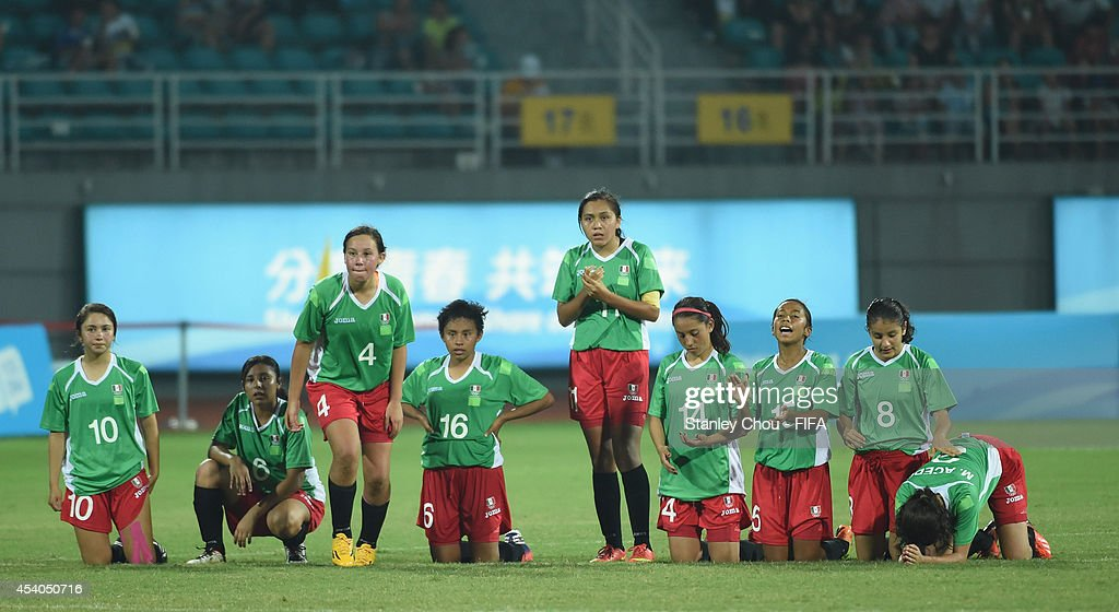 Mexico players wait during the penalty shoot out during the 2014 FIFA Girls Summer Youth Olympic Football Tournament Semi Final match between Venezuela and Mexico at Wutaishan Stadium on August 23, 2014 in Nanjing, China.