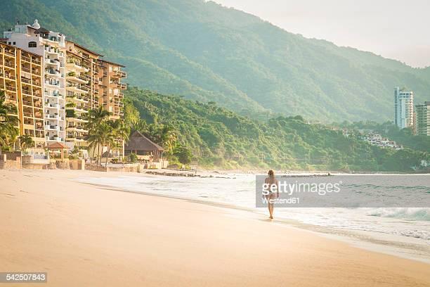 Mexico, Puerto Vallarta, woman wearing bikini walking at the Punta Negra beach