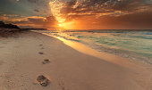 Mexico, Riviera Maya, Akumal beach, View along coastline with footprints in sand at sunrise