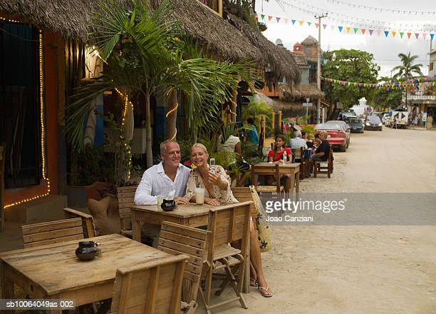 Mexico, Sayulita, couple sitting at outdoor restaurant photographing selves with digital camera