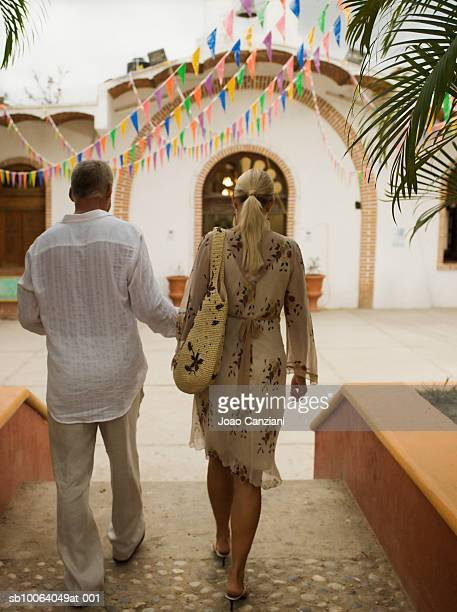 Mexico, Sayulita, couple walking on street, rear view