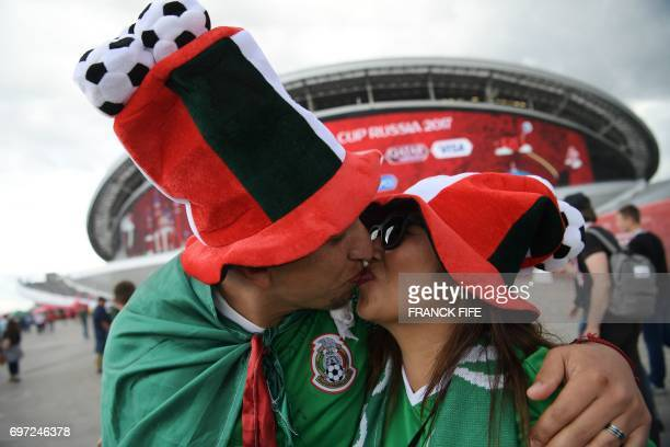 TOPSHOT Mexico supporters kiss outside the Kazan Arena ahead of the 2017 Confederations Cup group A football match between Portugal and Mexico in...