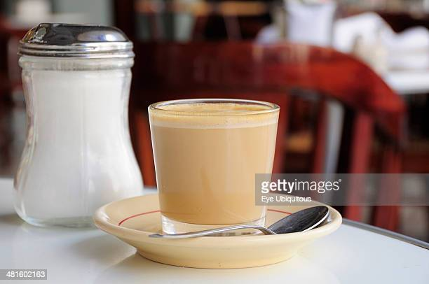 Mexico Veracruz Cafe con leche Coffee with milk served in glass with saucer and spoon on table beside sugar canister