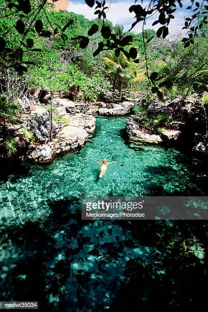 Mexico, Xcaret, Woman swimming in the river