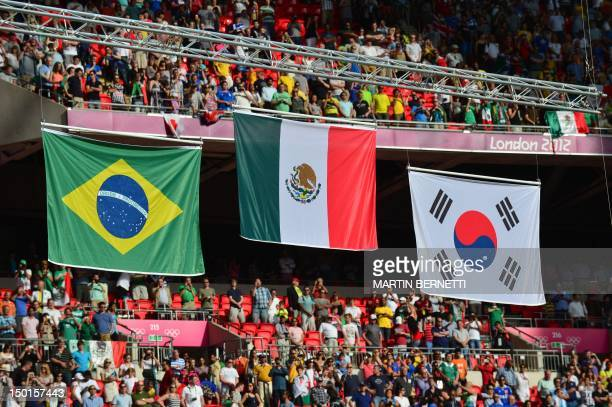 Mexico's Brazil's and South Korea's flags are raised during the podium ceremony after the football match Mexico vs Brazil at the London Olympic Games...