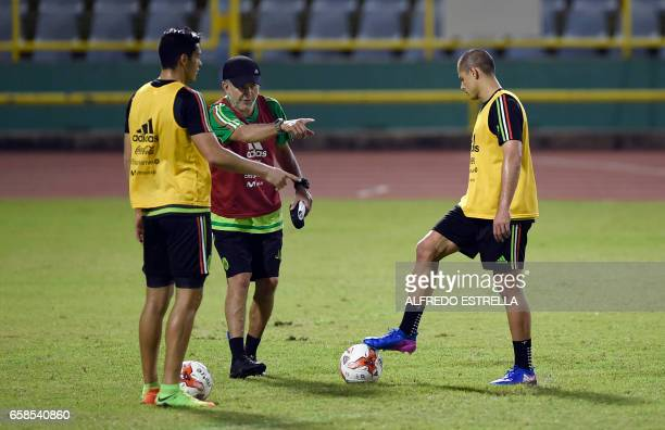 Mexico's coach Juan Carlos Osorio gives instructions to his player Ricardo Jimenez and Javier Hernandez during a training session at the Hasely...