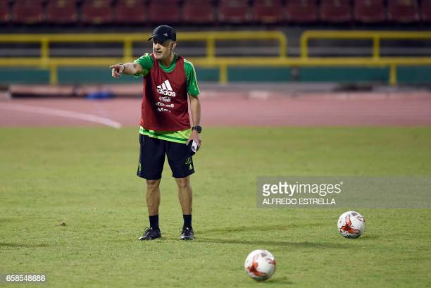 Mexico's coach Juan Carlos Osorio gives instructions to his players during a training session at the Hasely Crawford Stadium in Port of Spain...