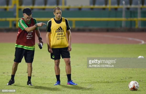 Mexico's coach Juan Carlos Osorio gives instructions to player Javier Hernandez during a training session at the Hasely Crawford Stadium in Port of...