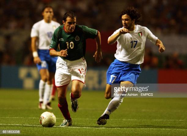 Mexico's Cuauhtemoc Blanco and Italy's Damiano Tommasi chase the ball