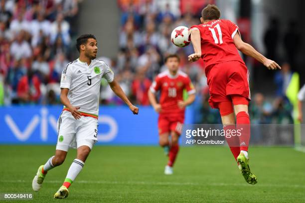Mexico's defender Diego Reyes eyes a header by Russia's forward Alexander Bukharov during the 2017 Confederations Cup group A football match between...