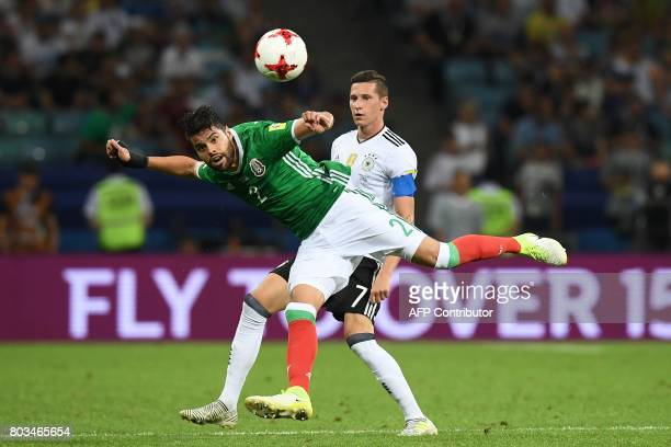 Mexico's defender Nestor Araujo heads the ball in front of Germany's midfielder Julian Draxler during the 2017 FIFA Confederations Cup semifinal...