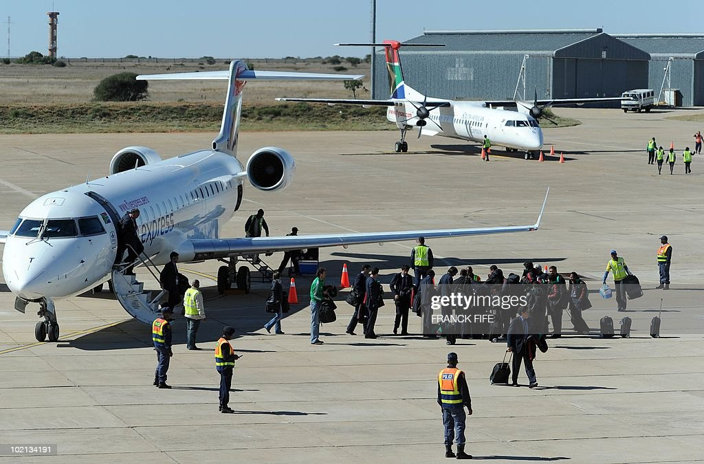 Mexico's football national team (R) disembark near the plane of France's team (R) at Polokwane airport, on June 16, 2010. France will play against Mexico in their second first-round match of the 2010 Football Wolrd Cup on June 17.