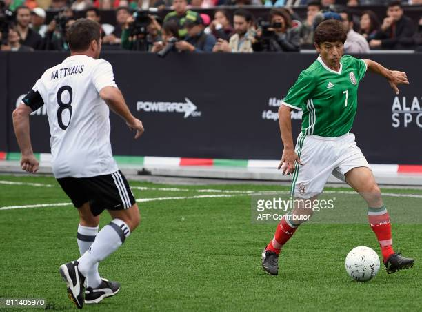 Mexico's former player Miguel Espana vies for the ball with Germany's former player Lothar Matthaus during an exhibition football match between...