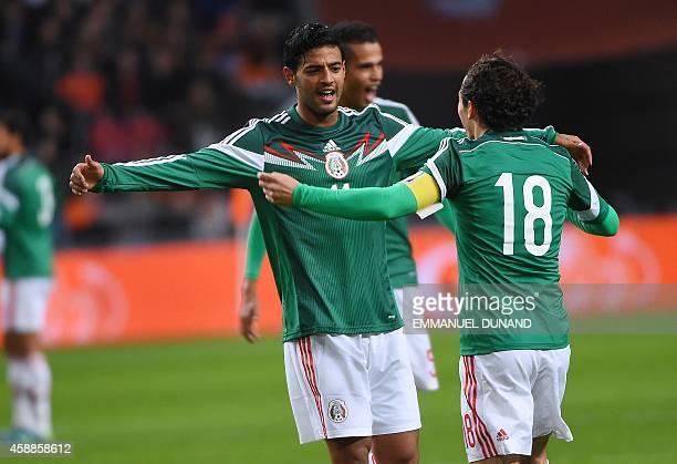 Mexico's forward Carlos Vela celebrates with Mexico's defender Andres Guardado after scoring the first goal during the friendly football match...