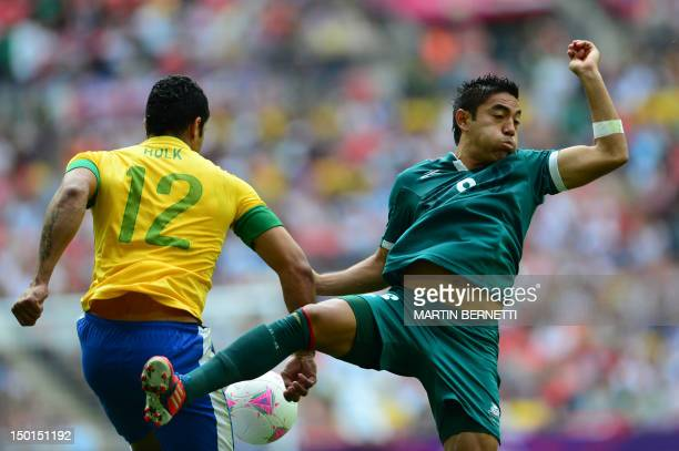 Mexico's forward Marco Fabian fights for the ball with Brazil's forward Hulk in the men's football final match between Brazil and Mexico at Wembley...