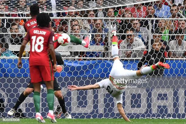 TOPSHOT Mexico's forward Oribe Peralta falls next to Portugal's forward Gelson Martins as Portugal's defender Nelson Semedo blocks his shot on goal...