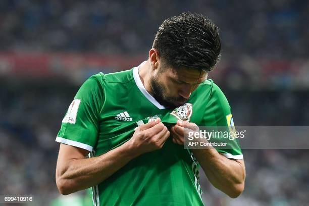Mexico's forward Oribe Peralta kisses his jersey celebrates after scoring a goal during the 2017 Confederations Cup group A football match between...