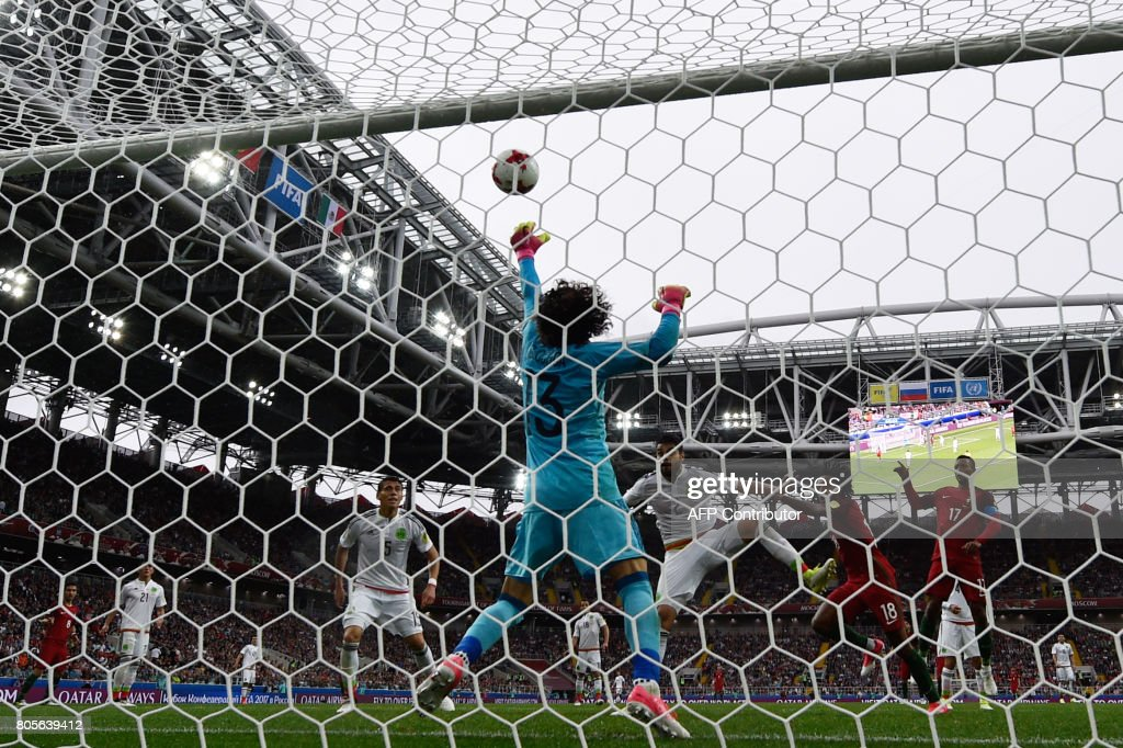 TOPSHOT - Mexico's goalkeeper Guillermo Ochoa (C) blocks a shot on goal during the 2017 FIFA Confederations Cup third place football match between Portugal and Mexico at the Spartak Stadium in Moscow on July 2, 2017. / AFP PHOTO / Alexander NEMENOV