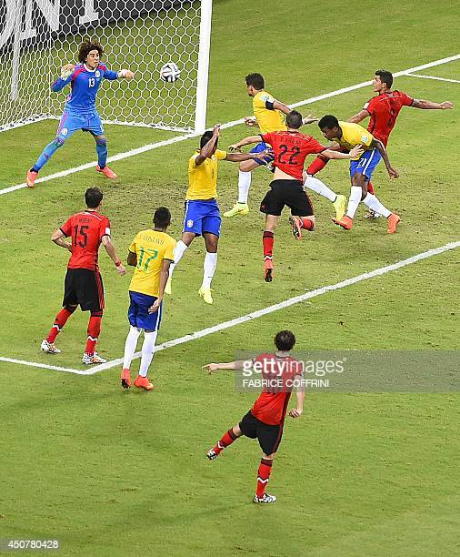 Mexico's goalkeeper Guillermo Ochoa saves a ball during a Group A football match between Brazil and Mexico in the Castelao Stadium in Fortaleza...