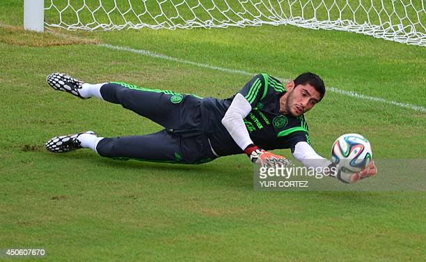 Mexico's goalkeeper Jose Corona stops the ball during a training session at the Frasqueirao ABC stadium in Natal Brazil on June 14 2014 AFP PHOTO/...