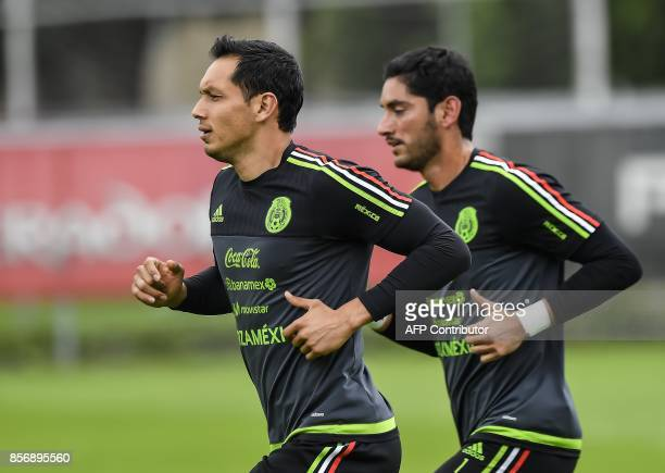 Mexico's goalkeepers Rodolfo Cota and Jesus Corona jog during a training session on October 02 2017 in Mexico City ahead of their upcoming 2018 FIFA...