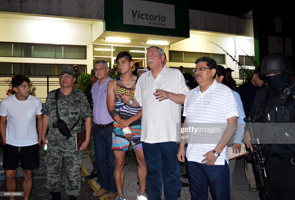 Mexico's Governor Egidio Torre Cantu (c) speaks to members of the press following the release of the Mexico football star Alan Pulido (4-l) on May 30, 2016 in Tamaulipas, after Pulido's kidnapping in his home state of Tamaulipas on May 29, according to authorities. Mexican security forces have rescued football star Alan Pulido, who was found 'safe and sound' hours after he was kidnapped in his crime-plagued home state of Tamaulipas, authorities said early May 30. Pulido, a former national team forward who plays for Greek club Olympiakos, declared he was 'very well, very well, thank God' as he appeared alongside Governor Egidio Torre Cantu at a brief news conference. / AFP / Luis Daniel Rios Martinez