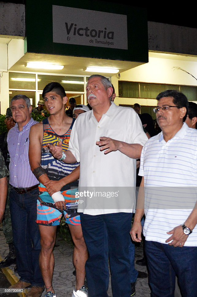 Mexico's Governor Egidio Torre Cantu (2-R) speaks to members of the press following the release of the Mexico football star Alan Pulido (2-L) on May 30, 2016 in Tamaulipas, after Pulido's kidnapping in his home state of Tamaulipas on May 29, according to authorities. Mexican security forces have rescued football star Alan Pulido, who was found 'safe and sound' hours after he was kidnapped in his crime-plagued home state of Tamaulipas, authorities said early May 30. Pulido, a former national team forward who plays for Greek club Olympiakos, declared he was 'very well, very well, thank God' as he appeared alongside Governor Egidio Torre Cantu at a brief news conference. / AFP / Luis Daniel Rios Martinez