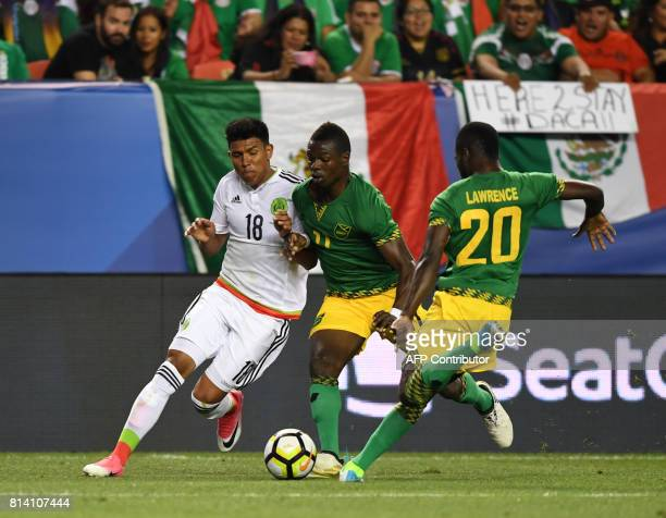 Mexico's Jesus Gallardo is tackled by Jamaica's Cory Burke and Kemar Lawrence during the Mexico vs Jamaica CONCACAF Group C Gold Cup soccer game on...