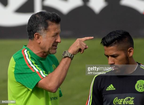 Mexico's national football team coach Juan Carlos Osorio gives instructions to player Javier Aquino during a training session ahead of their World...