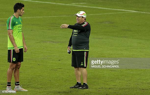 Mexico's national football team coach Miguel Herrera speaks to player Raul Jimenez during a training session at the Allianz Park in Sao Paulo Brazil...