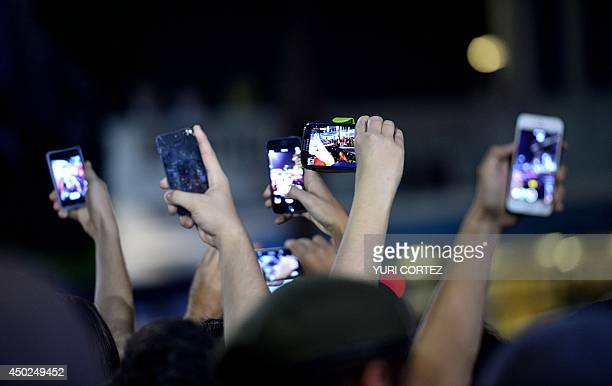 Mexico's national football team fans record with their mobile phones the arrival of their team outside of a hotel in Santos Sao Paulo Brazil on June...