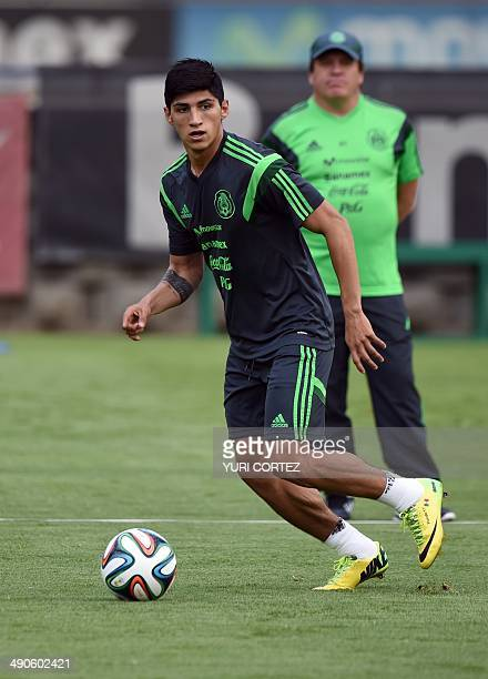 Mexico's national football team forward Alan Pulido controls the ball while coach Miguel Herrera observes during a training session at the High...