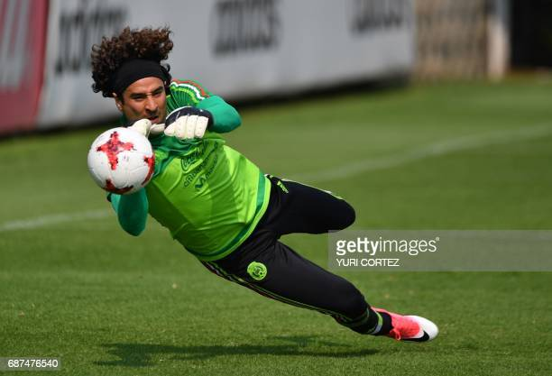 Mexico's national football team goalkeeper Guillermo Ochoa attempts to stop the ball during a training session ahead of the World Cup qualifier...