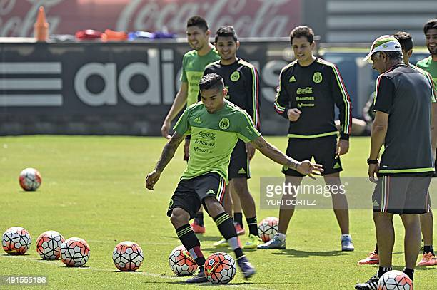 Mexico's national team midfielder Javier Aquino kicks the ball next to teammates and coach Ricardo Ferreti during a training session at the High...