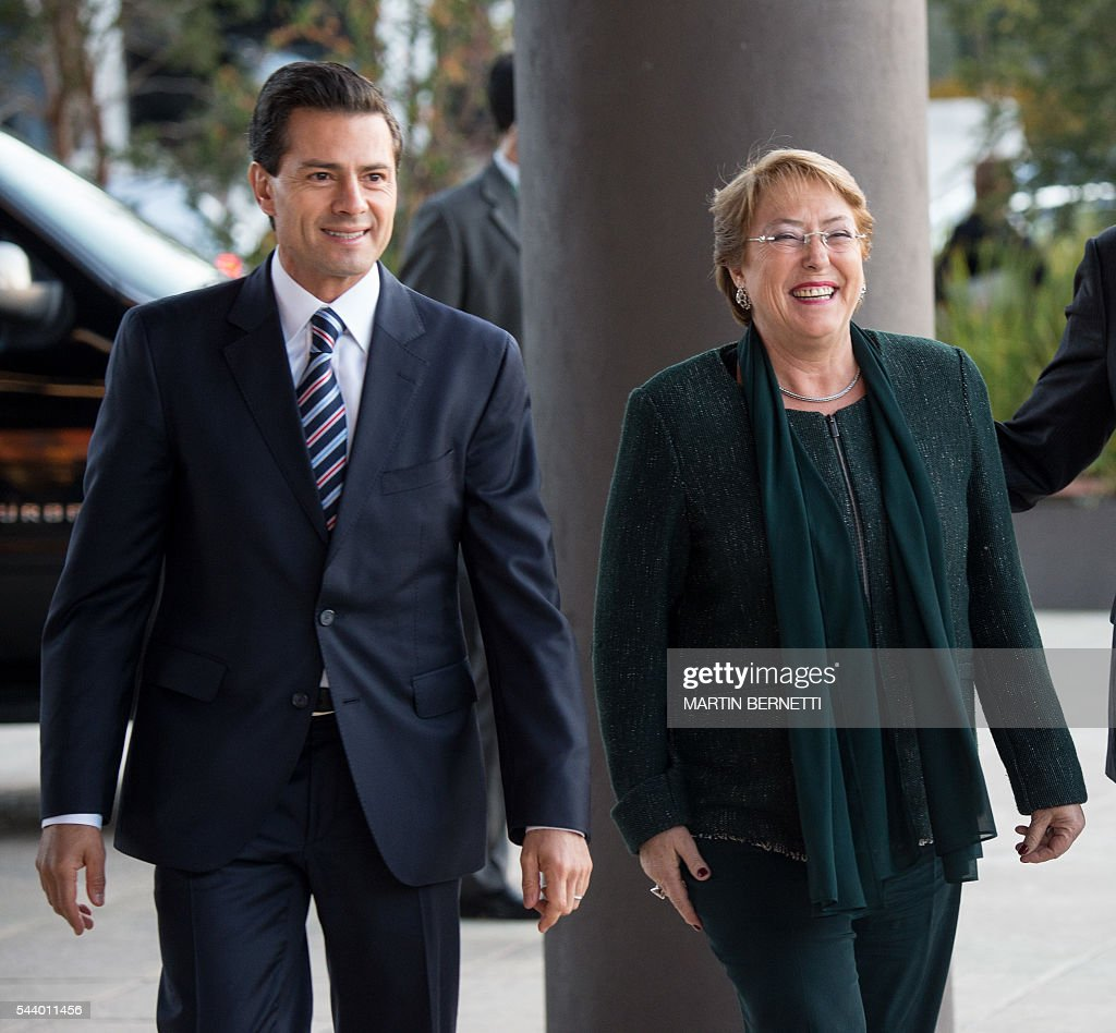 Mexico's President Enrique Peña Nieto (L) and Chile's President Michellle Bachelet arrive for a meeting of the III Pacific Alliance Business Summit in Frutillar, 1100 km south of Santiago, Chile, on June 30, 2016. / AFP / Martin BERNETTI