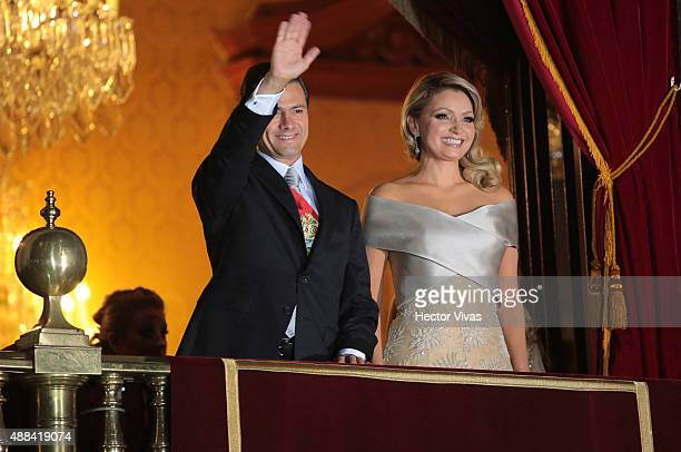 Mexico's President Enrique Pe–ña Nieto and his wife first lady Angelica Rivera greet the crowd after giving the traditional 'El Grito' during the...