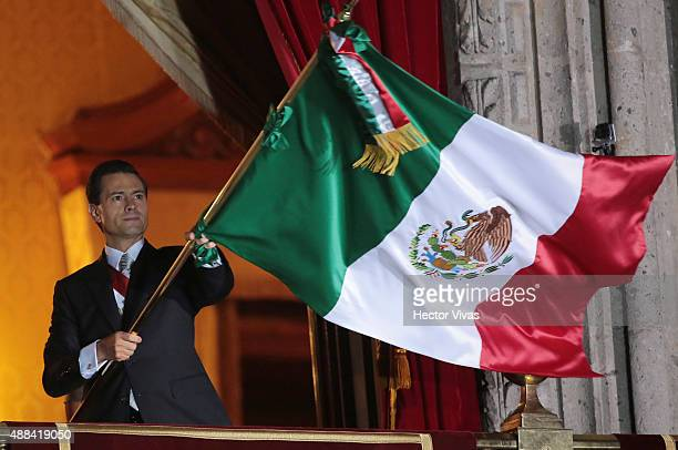 Mexico's President Enrique Peñ–a Nieto waves a Mexican flag after giving the traditional 'El Grito' during the anniversary of the 'Grito de Dolores'...