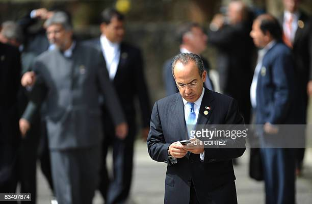 Mexico's President Felipe Calderon checks his mobile phone before the family photograph of the XVIII Ibero American Summit in San Salvador on October...