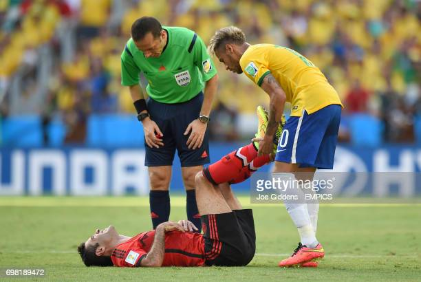 Mexico's Rafael Marquez receives treatment for cramp from Brazil's Neymar