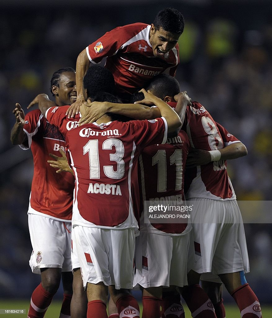 Mexico's Toluca forward Carlos Esquivel (bottom-2nd-R) celebrates with his teammates after scoring a goal against Argentina's Boca Juniors during their Copa Libertadores 2013 Group 1 football match at 'La Bombonera' stadium in Buenos Aires, Argentina, on February 13, 2013.