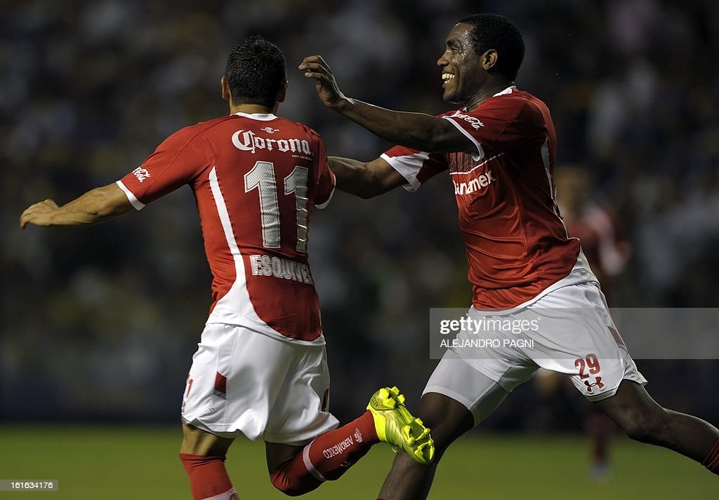 Mexico's Toluca forward Carlos Esquivel (L) celebrates with teammate forward Luis Tejada after scoring against Argentina's Boca Juniors during their Copa Libertadores 2013 Group 1 football match at 'La Bombonera' stadium in Buenos Aires, Argentina, on February 13, 2013. AFP PHOTO / ALEJANDRO PAGNI