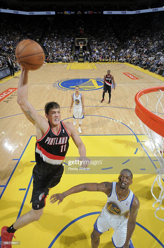 Meyers Leonard #11 of the Portland Trail Blazers dunks against Harrison Barnes #40 of the Golden State Warriors on March 30, 2013 at Oracle Arena in Oakland, California.
