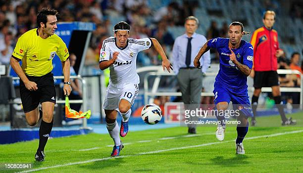 Mezut Ozil of Real Madrid duels for the ball with Alexis Ruano of Getafe as head coach Jose Mourinho looks on during the la Liga match between Getafe...