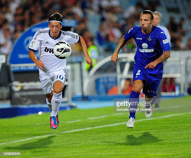 Mezut Ozil of Real Madrid duels for the ball with Alexis Ruano of Getafe behind head coach Jose Mourinho during the la Liga match between Getafe and...