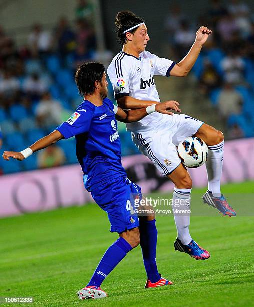 Mezut Ozil of Real Madrid duels for the ball with Miguel Torres of Getafe during the la Liga match between Getafe and Real Madrid at Coliseum Alfonso...