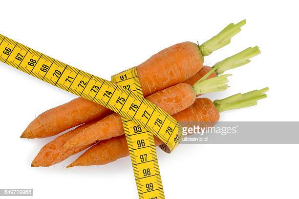 Möhren aus biologischem Anbau mit Massband Symbolfoto für gesunde Diät