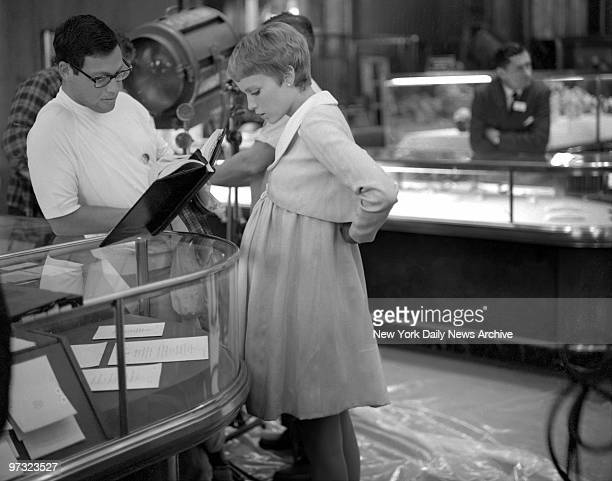 Mia Catches Camera's Eye On Fifth Ave Mia Farrow who plays a woman about to have a baby goes over her lines with script man inside Tiffany's The...