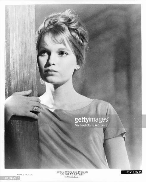 Mia Farrow with her hand around wooden post in a scene from the film 'Guns At Batasi' 1964