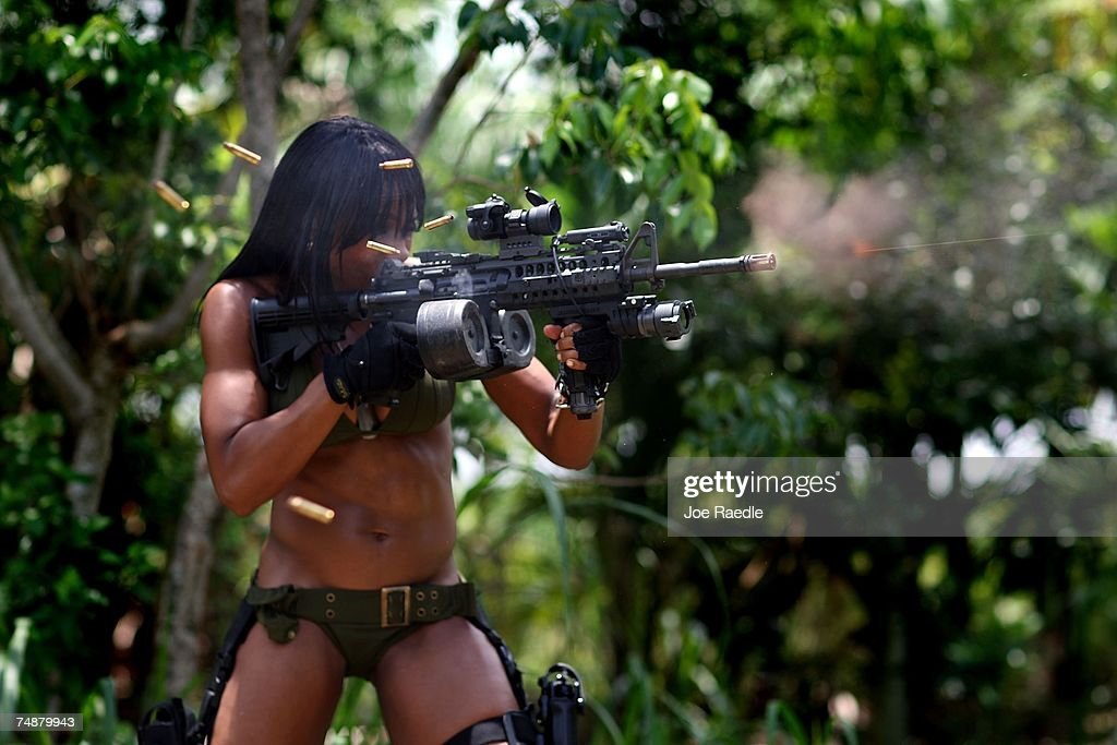 Mia Lawrence fires her weapon at a target as she competes against three other women on the set of Girls and Guns a webbased reality show featuring...