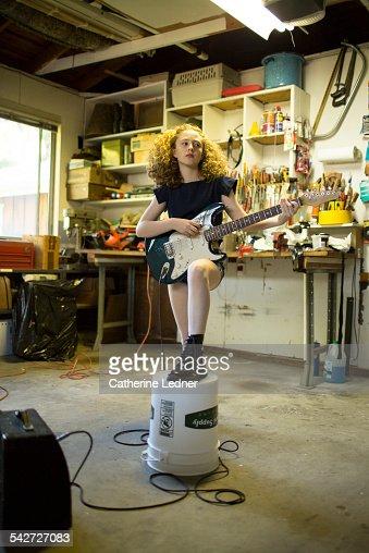 Mia playing electric guitar in garage
